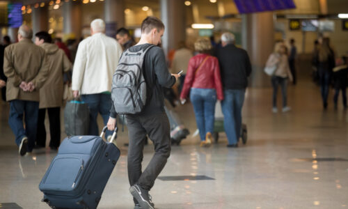 Back,View,Of,Young,Handsome,Traveler,Walking,In,Modern,Airport